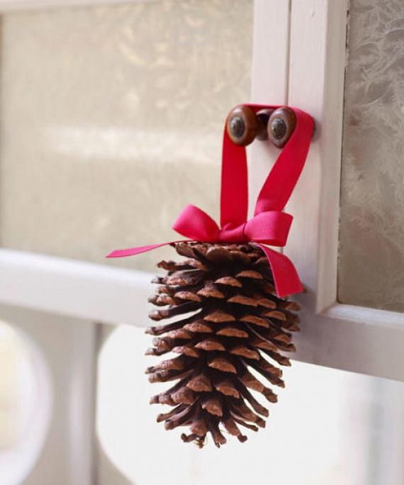 Egyszerű ajtó- vagy karácsonyfadíszt készíthetsz pár toboz és selyemszalag segítségével. A szalagból formázz masnit, majd ragasztóval erősítsd rá a toboz aljára, és már készen is van!