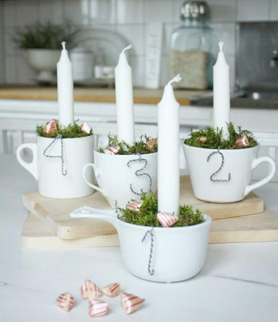 Ha van négy fehér csészéd, akkor ezekbe vágj virágoázis-darabokat, szúrj mindegyikbe egy-egy gyertyát, és takargasd le gondosan mohával. Már készen is vagy, de ha még szeretnéd fokozni, akkor kartonból kivágott számokat is akaszthatsz a csészékre.