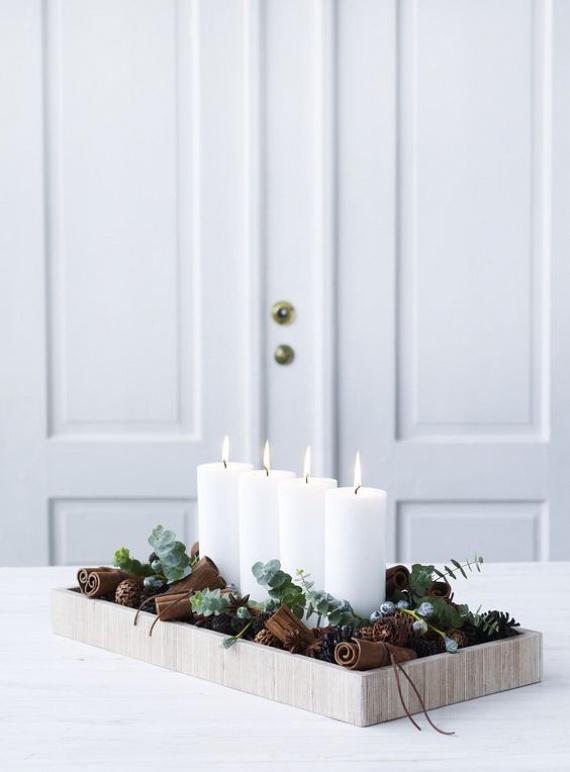 A minimalista adventi koszorúnak egy szép példáját láthatod a képen. Ehhez egy szögletes tálca közepére sorakoztass négy fehér gyertyát, rendezz köréjük fenyőágakat és fahéjrudakat vagy tobozokat. Ezután már csak az asztalra kell helyezned.