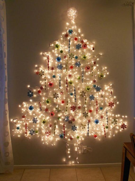 Ehhez a csillogó, ezer fényben pompázó karácsonyfához csupán egy sor hófehér, szépen fénylő izzóra és pár kiszuperált gömbre lesz szükséged. Az égősort fenyőfa formában rögzítsd a falra, majd akaszd rá a különböző formájú és színű dekorációs elemeket.