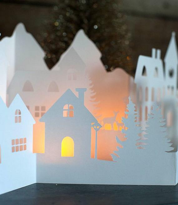Fehér papírból és néhány teamécsesből egy ilyen hangulatosan megvilágított erdőszéli falucskát is készíthetsz, amely az ablak vagy bármelyik polc dísze lehet a lakásban. A ragyogó faludoboz, a fény és az árnyékok játéka garantáltan még meghittebbé varázsolja a hangulatot.