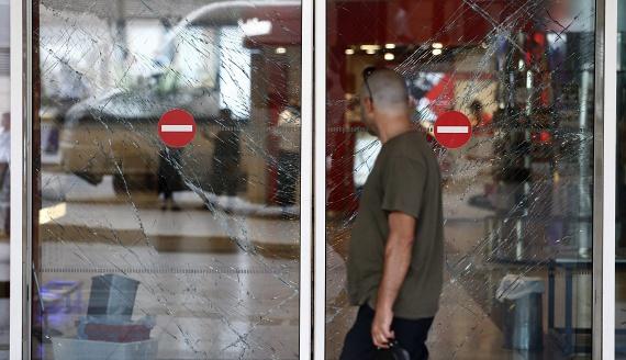Egy férfi nézi a betört üveget. A terroristák nem jutottak be az épületbe, egy rendőr lelőtte az egyiküket, aki így nem jutott át a kapun, viszont felrobbantotta magát. A rendőr nagy valószínűséggel életét vesztette, viszont sokakét megmentette.