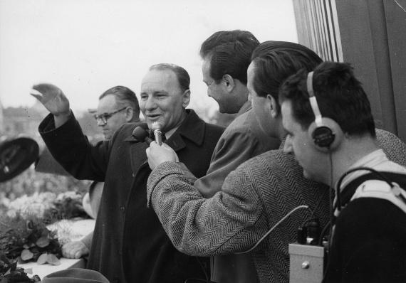 A mai Ötvenhatosok terén felállított dísztribünön mosolyogva integet Kádár János, közben pedig készül az interjú. 1960-ban járunk.