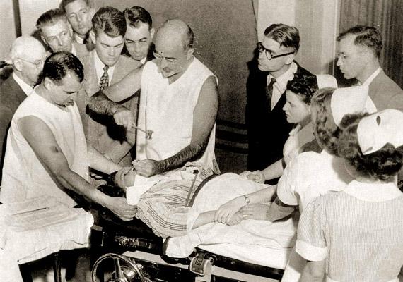 Bizonyára hallottad már a kifejezést: lobotómia. Az eljárás szülőatyja Walter Freeman - 1895-1972 -, a fenti képen ő végzi a mentális problémák kezelésére szolgáló beavatkozást. A lobotómiát egy jégcsákányhoz hasonló eszközzel végezték, amit a szemhéjon keresztül az agyba vezettek. A kevés sikeres eset mellett az okozott károk az 1940-es évek végére nyilvánvalóvá tették, hogy ez nem megfelelő kezelés. Tudj meg többet róla!