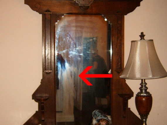 A ház egy másik szobájának ódon tükrében fotózták a fehér ruhás alakot: ruhája hosszú, hálóruhaszerű, haja sötét.