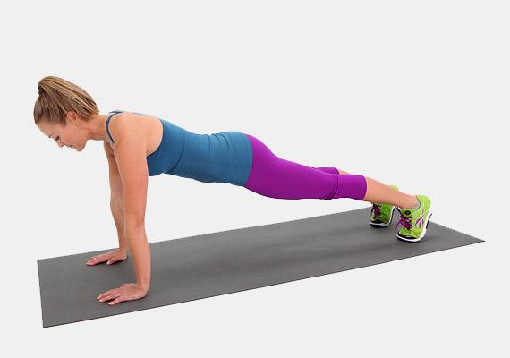 A fenti képen a legismertebb, alapvető plank gyakorlatot láthatod. Helyezkedj el vízszintes testhelyzetben: támaszkodj a tenyéren és a lábujjakon. A tenyerek a váll alatt legyenek, a lábak teljesen kinyújtva - mintha fekvőtámaszt végeznél. Ügyelj arra, hogy se a fejed, se a csípőd ne essen le - a tested fejtől a sarokig egy síkban helyezkedjen el. Ha a derekad érzékeny, feszítsd meg a farizmokat - így tehermentesítheted. Kezdetben napi 10 másodpercig tartsd ki a gyakorlatot, majd naponta emeld az adagodat néhány másodperccel.