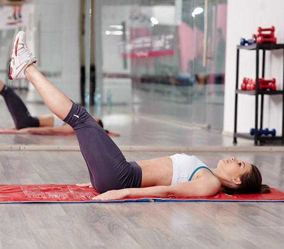 A második mozdulatsorhoz továbbra is maradj hanyatt fekve, és hagyd a tenyereidet lefelé fordítva a feneked mellett. A két lábadat zárd össze, emeld felfelé, amíg nem állnak derékszögben a talajhoz képest, majd vidd őket ismét lefelé, amíg el nem érik a padlóval párhuzamos, fekvésszerű tartást. Fontos, hogy ebben az állapotban ne fektesd le a lábaidat a földre, csak a gyakorlat végeztével!