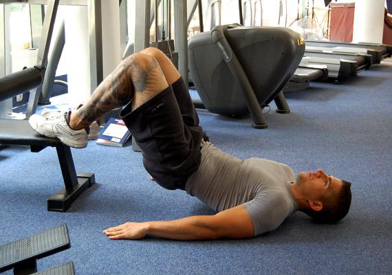 A sima felülésnél hatékonyabb és izgalmasabb a képen látható gyakorlat. Helyezkedj el hanyatt fekvésben, a térdeket húzd fel, és tedd egy körülbelül 30 cm magas, stabil tárgyra. Lassan emeld meg a csípődet.
