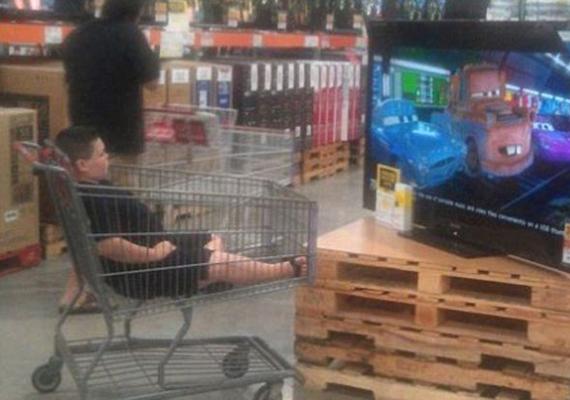 A gyerek egy bevásárlókocsiban bűvöli a varázsdobozt, amíg szülei a fogyasztói társadalom oltárán áldoznak. Jobban járna, ha focizna a többiekkel.