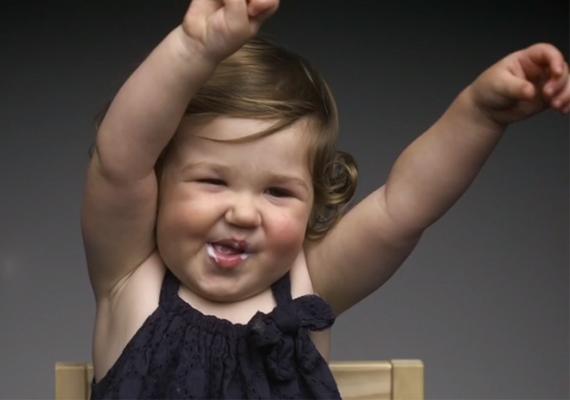 Ez a vidám kislány joghurtot ízlelget, életében először, és szemmel láthatóan tetszik neki.