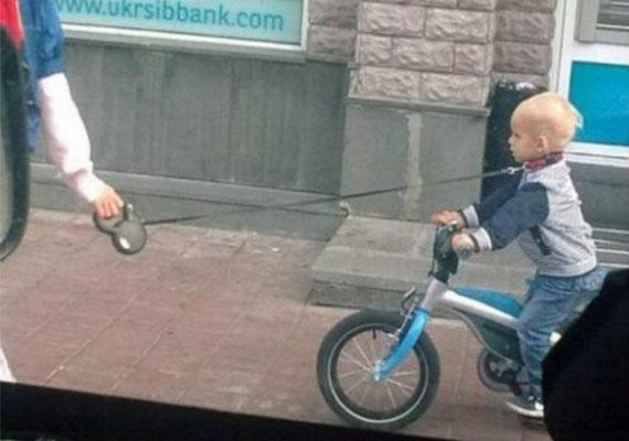 Ez a másik szülő pórázon vezeti bicikliző gyerekét.