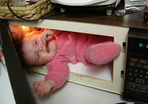 Hogy kerül egy kicsi a mikróba? A gyerek láthatóan nem élvezi a szülő szerint nagyon mókás dolgot.