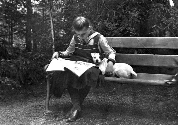 A kislány és kutyája egy meghitt pillanatát megörökítő fotó az első világháború második évében, 1915-ben készült. Vajon miről olvas az újságban?