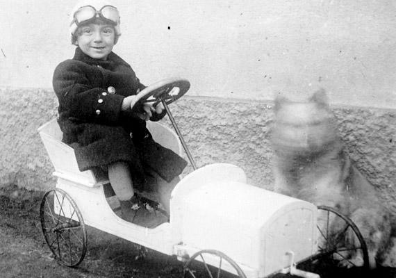 Az 1911-ben készült fotó címe akár szellemkutya is lehetne. Bár valószínűbb, hogy a játékautóban ülő kisfiú négylábú barátja csupán bemozdult.