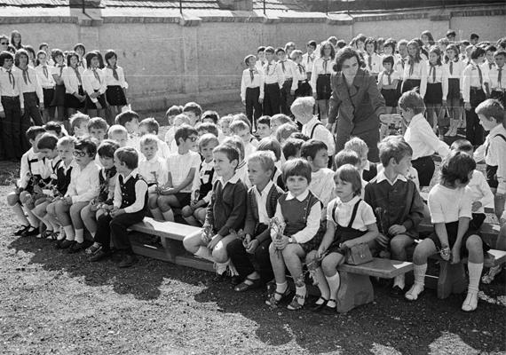Általános iskolás gyereksereg egy iskolai ünnepségen, a háttérben úttörőkkel. A rendszerváltás óta az úttörőlét is sokat változott, számuk ma már elenyésző, és az úttörőség jellege is más. (1972)