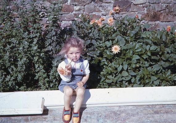 Akkor még többet játszottak a levegőn a gyerekek. Ez a bájos kislány például egy szép virágot csodál. (1970)
