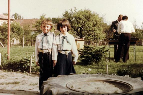 A '80-as évek két kis úttörője, akik a kisdobosavatás után fotózkodtak az iskola udvarán.                         (1983)