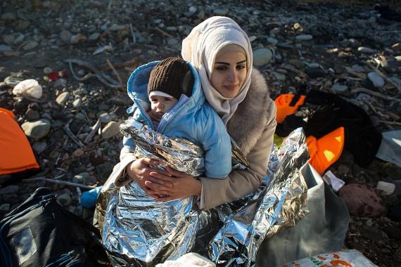 Egy menekült édesanya csecsemő kisfiával ül a földön Leszbosz szigetén. Az anya körbetekeri gyermekét melegen tartó fóliával. A hideg évszak beköszönte még jobban megviseli a menekülőket, az édesanyák mégis inkább a hideget és a veszélyes hajóutat választják, hogy a gyerekeiknek majd jobb legyen.