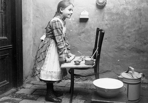 Egy kislány a játék konyhájában szorgoskodik - 1913.