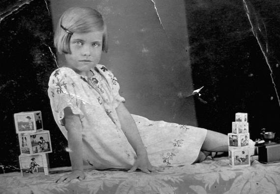 1934-ben készült a fotó, amelyen ez a gyönyörű kislány pózol illedelmesen a kockái mellett. Ezekből a kockákból tornyot lehetett építeni, és ha megfelelő sorrendben raktad ki a formákat, egy mese rajzolódott ki az oldalukra rajzolt képekből.