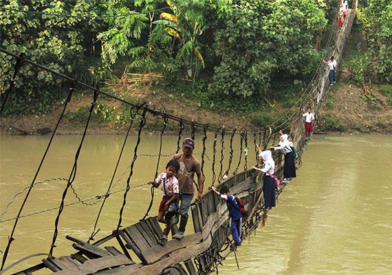A képen indonéz gyerekek mennek át egy folyó felett egy rozoga kötélhídon.