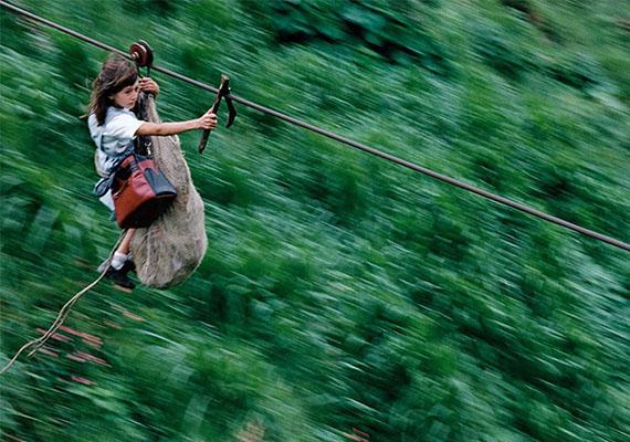 Egy kislány a kolumbiai Rio Negro felett siklik az iskola felé.
