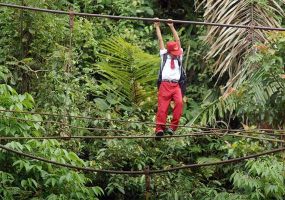 Egy szumátrai kisfiú csimpaszkodik és egyensúlyoz, hogy eljuthasson az iskolába.