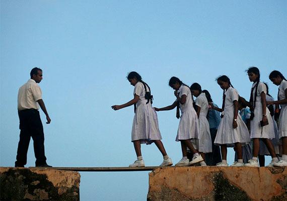 Diáklányok egyensúlyoznak egy pallón Srí Lankában.