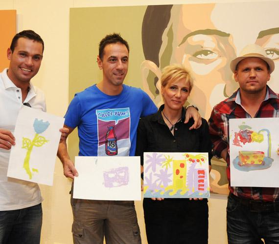 A csapat büszkén mutatja festményeiket.