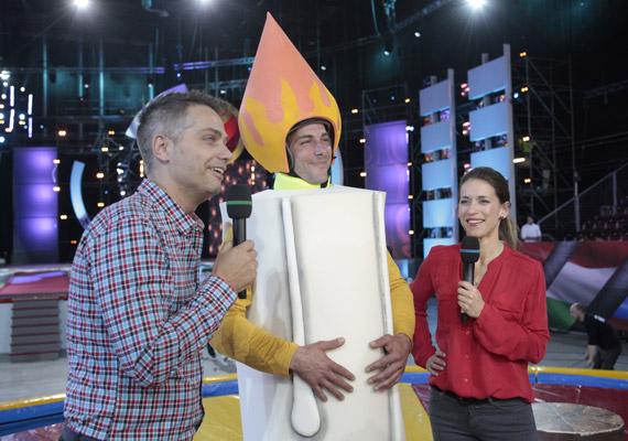 Harsányi Levente és Varga Edit műsorvezetők egy gyertyának öltözött versenyzővel.