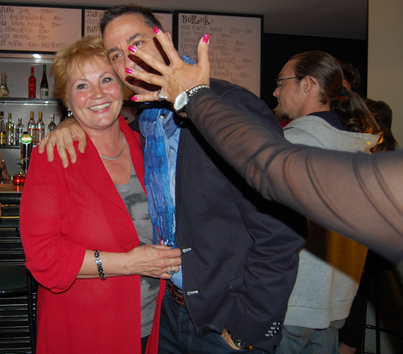 Bay Éva legendás bemondó-műsorvezetőnő Csonka Andrással fotózkodott, amikor Szulák Andrea észrevette őket, és örömében kitárta feléjük a karját.
