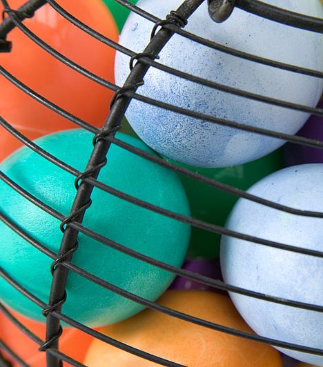 Színes tojások mutatós tálbanHa kissé vidékies jellegű az otthonod berendezése, a tojásokat akár papírtartóban is az asztalra helyezheted. Ha azonban mutatósabb asztaldíszre vágysz, keress számukra egy nagyobb, gömb alakú üvegvázát vagy drótkosarat.