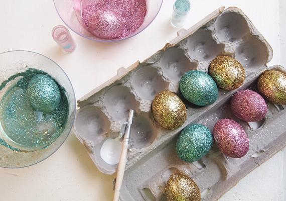 Csillámot is használhatsz a díszítéshez. Egyszerűen forgasd bele a megragasztózott tojásokat a glitterbe - hasznos, ha kifújt tojással dolgozol, illetve beleszúrsz a lyukba egy hurkapálcát, mert így nem leszel nyakig maszatos -, és hagyod, hogy megszáradjanak.