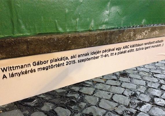 A plakát alatti felirat magyarázatképpen szolgál az arra járó nézelődőknek:                         Wittmann Gábor plakátja, aki annak idején párjával egy ARC kiállításon randizott először. A lánykérés megtörtént 2015. szeptember 11-én, itt a plakát előtt. Szilvia igent mondott. :)                         Sok boldogságot kívánunk!