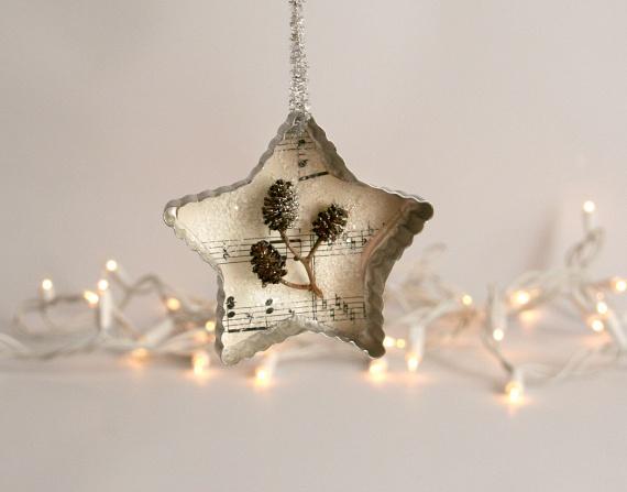 A fotón látható karácsonyi dísz kivitelezése talán egy picit bonyolultabbnak tűnik, mégis egyszerű az elkészítése. Ebben az esetben egy rég nem használt kottafüzet darabját, hófehér csillámot, pár apró tobozt és díszes madzagot használj: a papírból kinyírt csillagot ragaszd a sütiszúróba, majd jöhetnek rá az apró tobozok, amiket végül csillámmal szórj meg. Az akasztóját ragasztóval erősítsd oda!