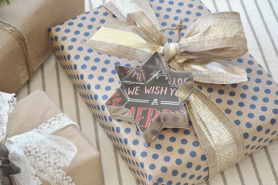 A kézzel csomagolt ajándékot egy hatalmas masnival és egy sütiszúróval teheted díszesebbé. Még elegánsabb lesz a végeredmény, ha a csillag formájú mézeskalácsformába valamilyen karácsonyi tematikájú papírdarabot ragasztasz.