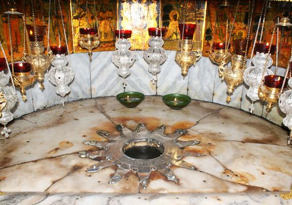 A barlang közepén egy csillag, illetve a belevésett szöveg jelzi, hogy hol született Isten fia.
