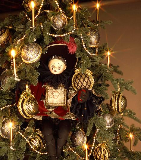 Babával  A gyertya alakú égők ünnepi fénybe borítják a fát, melyet a képen törzs helyett egy szomorú porcelánbaba tart. Meglehetősen extrém kombináció.  Kapcsolódó cikk: Illatos karácsonyi dekorációk »