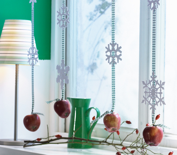 Az ablakkeretre erősített füzérek közül ez az egyik legmutatósabb. A hosszú szalagokra erősíts pehelydíszeket, az aljukra pedig köss almát. Egyszerű, mégis nagyszerű választás.