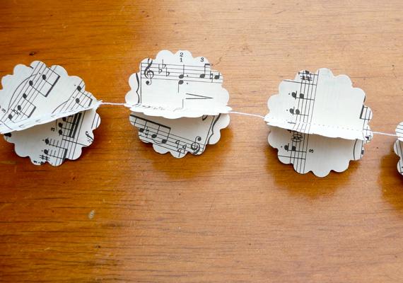 Vágj ki egy pár tetszőleges formát bármilyen papírból, és a közepén varrd össze. Hagyj egy pici hurkot a tetején a cérnából, nyisd négyfelé a díszt, és már fel is akaszthatod.