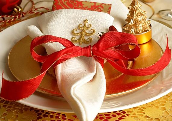 A fehér és arany tányér jellegzetes kontrasztja a hímzett és masnival átkötött szalvétával bájos benyomást kelt.