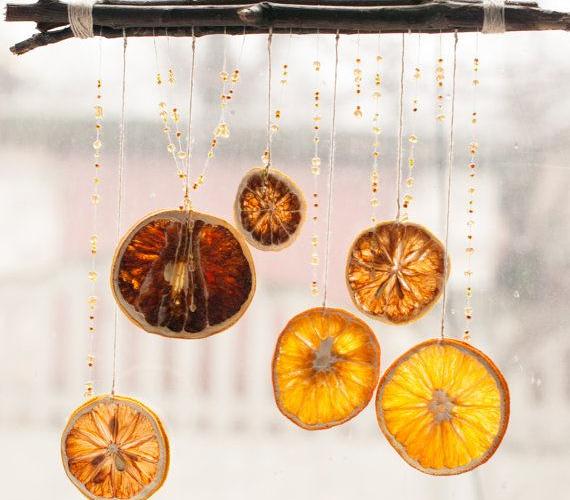 És még egy hasonlóan egyszerű megoldás: botra függeszd fel a madzagra fűzött narancskarikákat. Rusztikus, de szép.