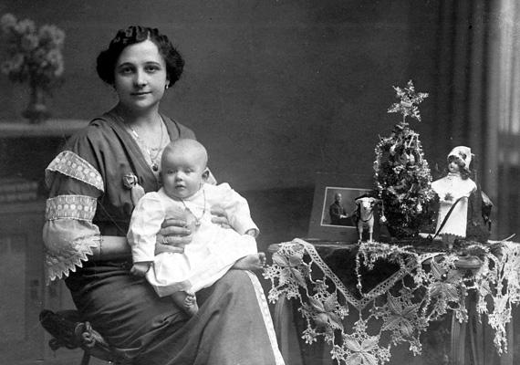 Egy ifjú anyuka a kisbabájával ünnepli a karácsonyt a századforduló utáni években, Budapesten. A papa nem látható - talán harcol valahol, esetleg el is esett.