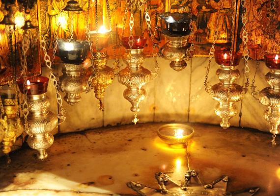 A barlangban tucatnyi mécses világítja meg a csillagot és a falon végigfutó, apostolokról készült ikonokat.