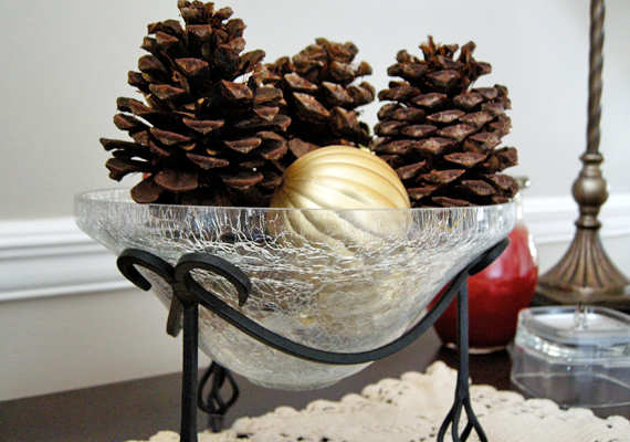 Három tobozból, egy aranyszínű karácsonyfadíszből és egy üvegtálból is csodás kompozíciót készíthetsz.