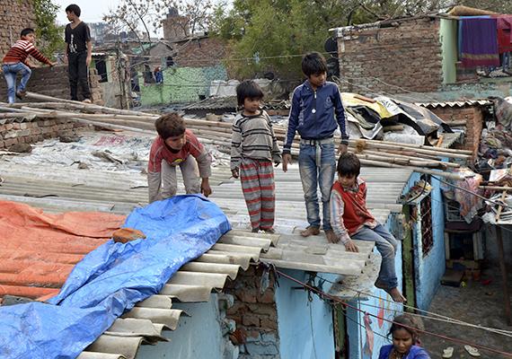 Gyermekek az indiai Új-Delhi legnagyobb nyomornegyedének háztetőin. A helyiek körülbelül 50%-a ilyen körülmények között él.