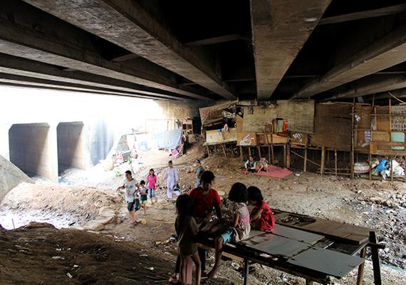 Gyermekek élnek és játszanak a híd alatt Jakartában, Indonéziában.