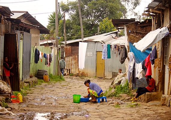 Egy kislány mosogat a házak között Etiópiában, Addis Ababa Lideta nevű körzetében.