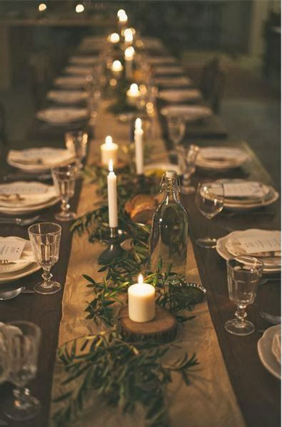 Egyszerűen tökéletes - olykor a kevés is több mint elég. Ezt a meghitt hangulatú dekorációt nagyon egyszerű előteremteni. Az asztal közepén hosszú futó van, természetes, natúr vászon anyagból. Gyertyatartók gyanánt fatörzsből vágott korongok vannak az asztalon, melyeket lazán körbefutnak az örökzöld ágacskák.