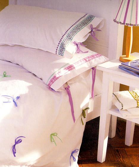 Bájos masnikAz egyszerű, fehér ágynemű és a fehér ágykeret teszi lehetővé, hogy ennyire különlegesen romantikus kiegészítők is jól mutassanak ebben a hálóban. A tavaszi mező színei az éjjelilámpa búrájáról köszönnek vissza.
